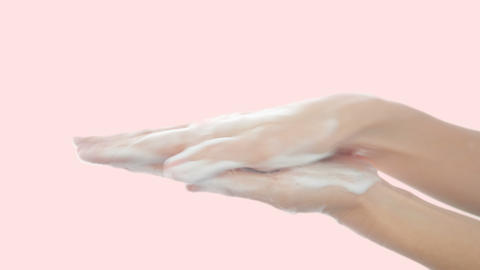 Woman hands washing with soap on orange pastel background for clean hygienic GIF