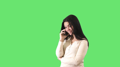 Smiling Caucasian woman with black hair talking on the phone at green background Live Action