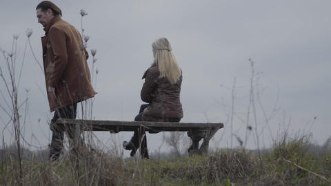 Adult Caucasian brunette man leaving blond slim woman alone on bench on lake Live Action