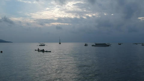 flying over water between boats and boats at sunset in cloudy weather Live Action