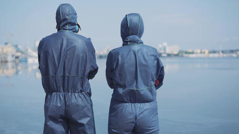 Back view of two people in biohazard suits standing at riverbank and looking at Live Action