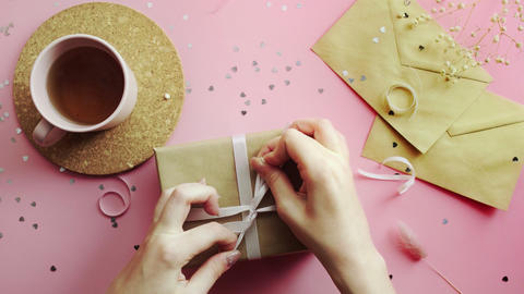 Female hands tying bow a Christmas gift wrapped in craft paper with white bow Live Action