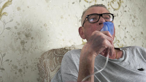 Elderly man does medical therapy steam inhalation at home Live Action