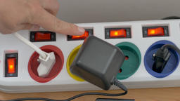 Hand is switching off power on the extension cord main switch. Energy savings Live Action