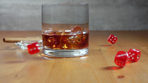 Glass of Whiskey on a Wooden Table and Dice. Slow Motion Live Action