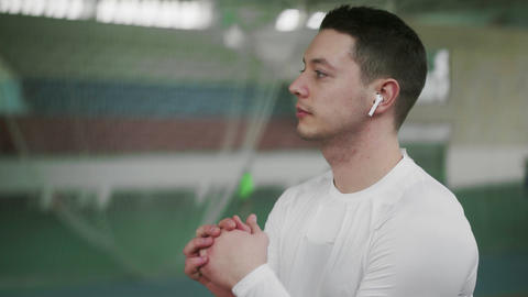 Young athlete male with wireless headphone warm up before sports exercise Live Action