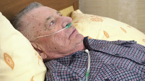 Elderly man is lying in bed at home with a medical oxygen catheter in his nose Live Action