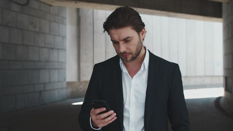 Portrait of excited business man reading good news on smartphone at urban street Live Action