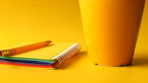 yellow color notepad with pencil and coffee mug on yellow background Live Action