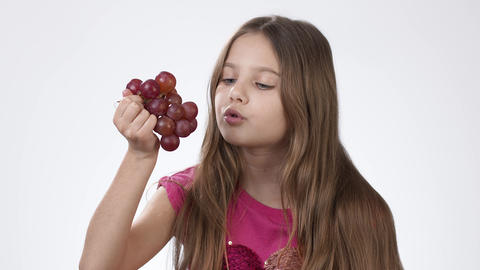 Little girl eating ripe big grapes on a white background. The girl appetizingly Live Action