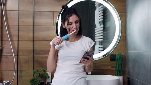 Likable joyful young black haired woman standing near the mirror and cleaning Live Action