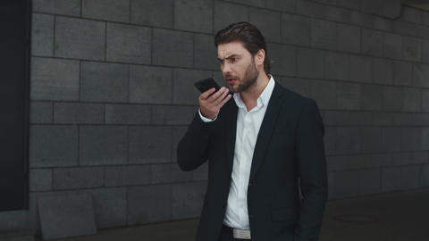 Serious business man recording audio message on smartphone outdoors Live Action