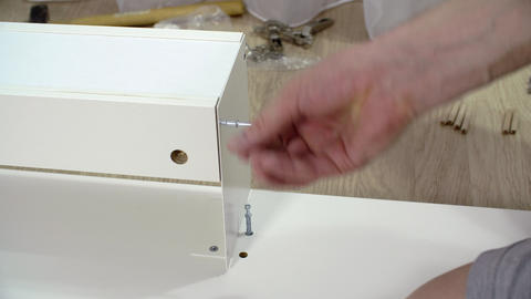 Man assembling home furniture with hexagon. Carpenter fixing furniture detail Live Action