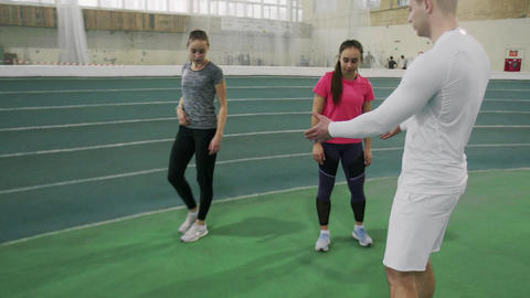 Sporty women is training with trainer, they making squats in runners arena Live Action