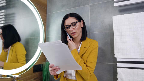 Confident smiling professional black haired female office manager reading Live Action