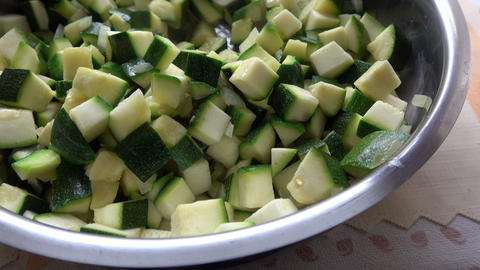 Vegetables cut in cubes fried on frying pan, in kitchen. Zucchini fried in cubes in a pan. Live Action