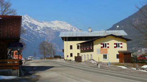 Car passing hotel and filling station, snowy mountains and blue sky background Footage