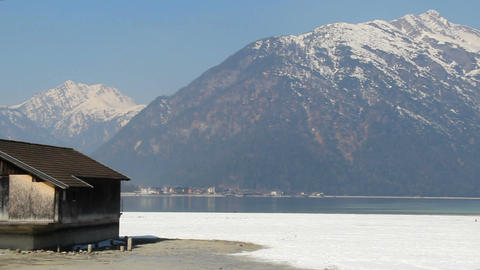 Abandoned wooden hut at lakeside, pan shot of majestic snowy mountain range Footage