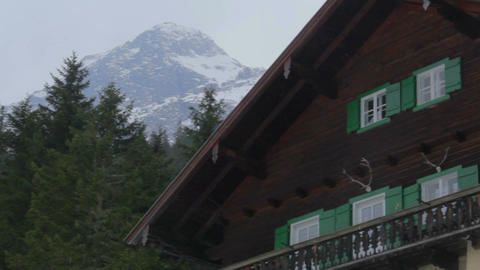 Establishing shot of nice wooden cottage in mountains, snowy rock on background Footage
