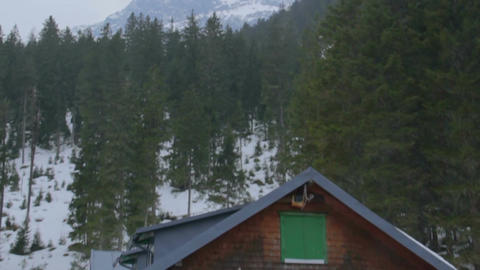 Establishing shot of private house at mountain bottom, snowy peak on background Footage