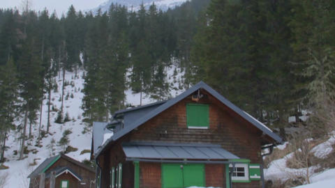 Abandoned wooden house in forest at bottom of mountains, avalanche danger Footage