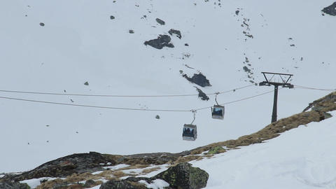 Two cable cars moving in opposite directions above rocky mountains, ski resort Footage