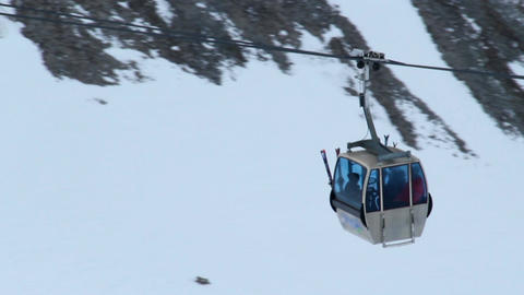 People sitting in cable car, moving up towards skiing run in snowy mountains Footage