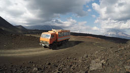 Expedition truck transportation tourists on mountain road on background volcanoe Footage