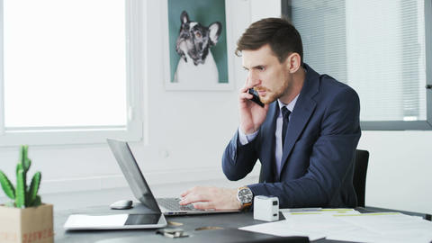 Young businessman talking via his mobile during work Footage