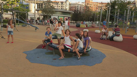 Active children playing on merry-go-round on playground, happy childhood Footage