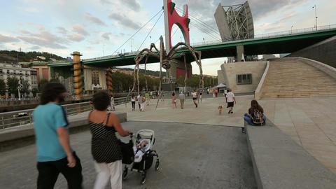 Many tourists strolling near huge spider sculpture, summer evening in Bilbao Live Action
