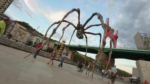 People strolling near Maman spider and La Salve Bridge, modern sculpture art Live Action