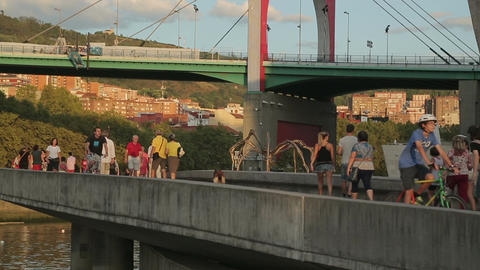 People walking bridge across river, viewing street art paintings, active life Footage