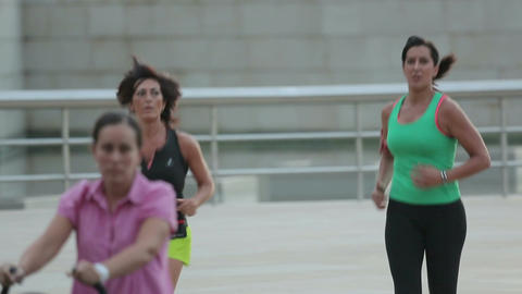 Two athletic women in sportswear running in public. Healthy active lifestyle Footage