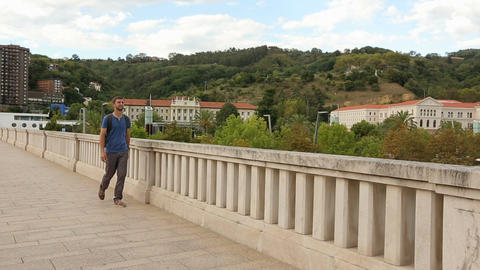 Male student with backpack stops to enjoy beautiful city view from the bridge Footage