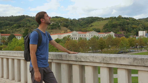 Young male tourist enjoying picturesque view and warm weather in Bilbao, Spain Live Action