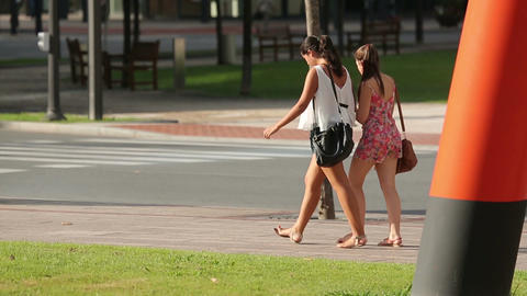 Couple of girls walking on the sidewalk, friends hanging out on sunny summer day Footage