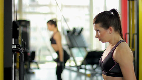 Beautiful young woman working out, strong female exercising on sports equipment Footage