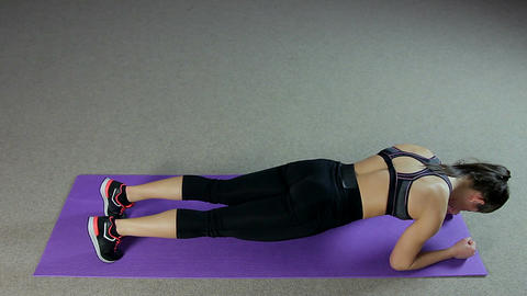 Woman starts and finishes doing a difficult plank exercise, training hard in gym Footage