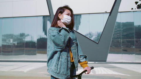 Young asian woman in a jeans jacket with the scooter wears a medical mask stands Live Action