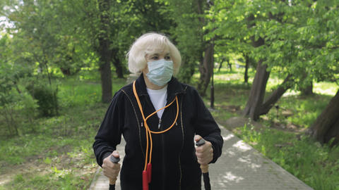 Active senior old woman in mask training Nordic walking in park at quarantine Live Action