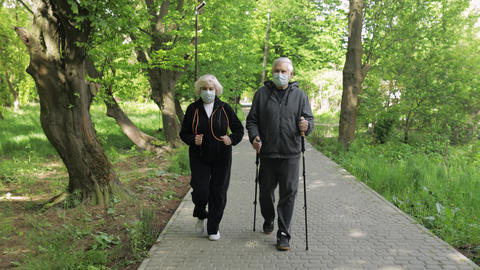 Active senior old man, woman training Nordic walking in park during quarantine Live Action