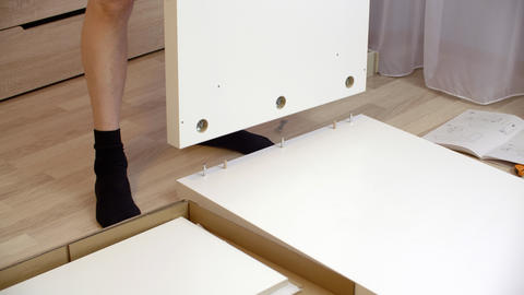 Man assembling new furniture for bed room on floor. Handyman collecting white GIF