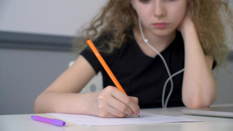 Curly girl teenager listening music in earphones and writing by pencil on paper Live Action