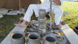 Potter sets the pottery wheel in motion and finish his work Acción en vivo