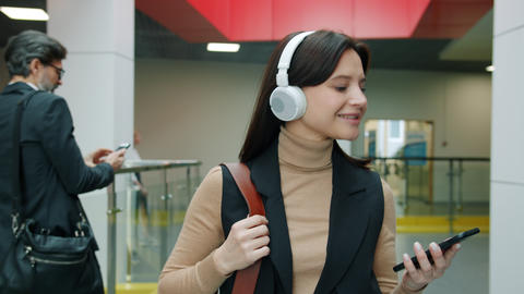 Cheerful young business lady walking in lobby wearing headphones using Live Action