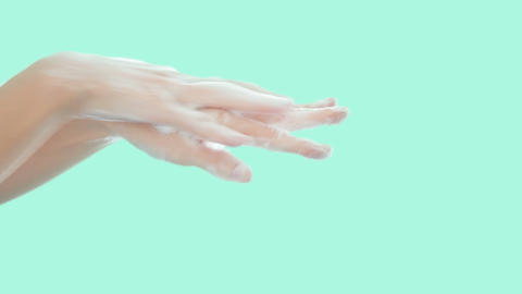 Female washing hands with soap on green pastel background for clean hygienic Live Action