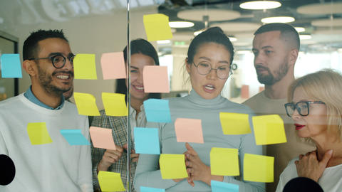 Cheerful people colleagues working in office with sticky notes talking laughing Live Action
