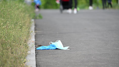 people throw away masks and gloves in parks and on the streets among people Live Action