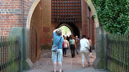 Tourists are watching gate over the main entrance to the Malbork castle Live Action